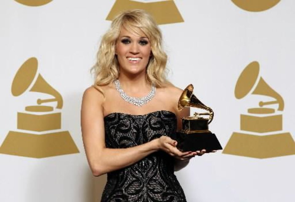 "Checotah native Carrie Underwood poses backstage with the award for best country solo performance for ""Blown Away"" at the 55th annual Grammy Awards on Sunday, Feb. 10, 2013, in Los Angeles. (AP)"
