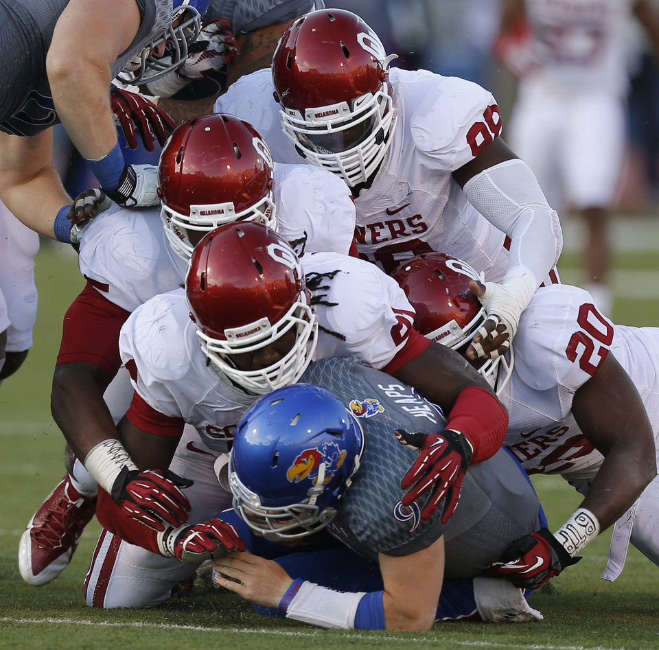 Photo - A group of Oklahoma defenders including, from top, Chuka Ndulue (98), Quincy Russell (95), Charles Tapper (91), and Frank Shannon (20), bottom right, bring down KU's Jake Heaps (9) during the college football game between the University of Oklahoma Sooners (OU) and the University of Kansas Jayhawks (KU) at Memorial Stadium in Lawrence, Kan., Saturday, Oct. 19, 2013. Oklahoma won 34-19. Photo by Bryan Terry, The Oklahoman