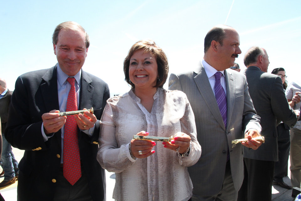 Photo - U.S. Sen. Tom Udall, left, New Mexico Governor Susana Martinez and State of Chihuahua, Mexico Governor Cesar Duarte, right,  show golden railroad spikes used during a railroad hub opening ceremony in Santa Teresa, New Mexico, Wednesday, May 28, 2014. A sprawling $400 million railroad hub opened in this border town and it is expected to create up to 600 jobs and attract businesses. (AP Photo/Juan Carlos Llorca)