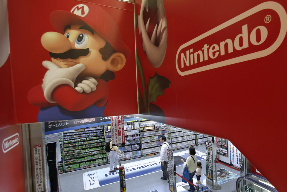 Photo - Shoppers walk under the logo of Nintendo and Super Mario characters at an electronics store in Tokyo Wednesday, May 7, 2014. Nintendo Co. sank to a loss for the fiscal year ended March as sales of its Wii U game machine continued to lag, but the Japanese manufacturer of Pokemon and Super Mario games promised Wednesday to return to profit this year. (AP Photo/Shizuo Kambayashi)