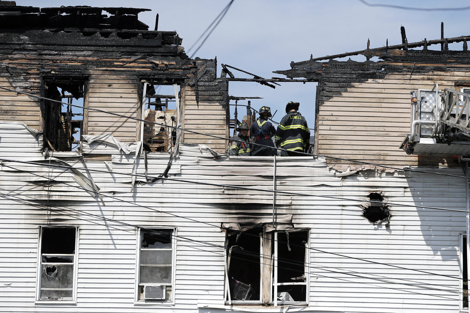 Photo - Firefighters work on the top floor inside a burned three-story apartment and business building in Lowell, Mass., Thursday, July 10, 2014, where officials said seven people died in a fast-moving pre-dawn fire. The victims' names were not immediately made public.  The cause and origin of the blaze remain under investigation, State Fire Marshal Stephen Coan said.  (AP Photo/Elise Amendola)