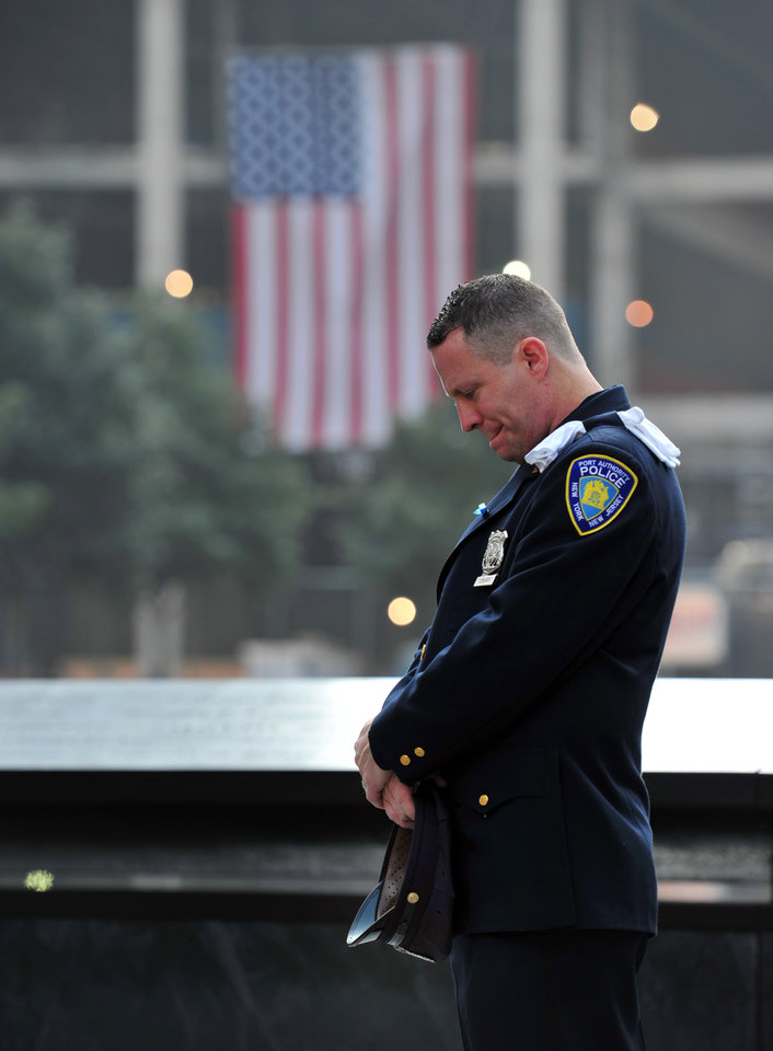 Photo - Daniel Henry, a Port Authority of New York/New Jersey police officer, pauses during a moment of silence at 9:01 a.m. at the south reflecting pool at the 9/11 Memorial on Wednesday, Sept. 11, 2013, during ceremonies marking the 12th anniversary of the 9/11 terrorist attacks in New York. (AP Photo/Stan Honda, Pool)