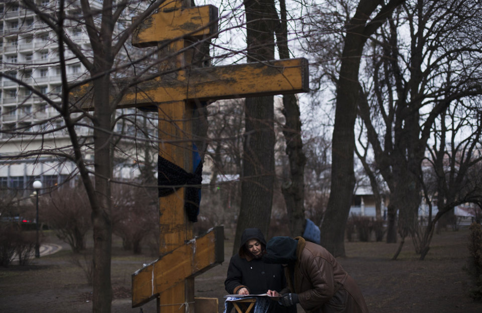 Photo - Women read prayers at a cross placed near the Parliament in Kiev Ukraine, Monday, March 17, 2014. Ukraine's political turmoil has become Europe's most severe security crisis in years and tensions have been high since Russian troops seized control of Crimea two weeks ago. (AP Photo/David Azia)