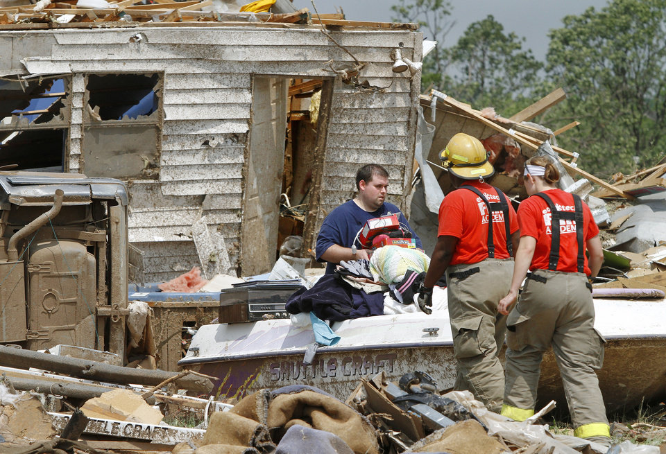 Photo - A person removes items from a damaged home. Residents of Steelman Estates in Bethel Acres sift through the remains of their homes on Monday, May 20, 2013, after a violent tornado ripped through the neighborhood yesterday, killing one man.    Photo  by Jim Beckel, The Oklahoman.