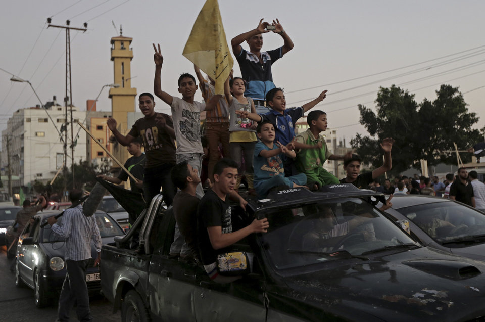 Photo - Palestinians celebrate the cease-fire between Palestinians and Israelis at the main road in Gaza, in the northern Gaza Strip, Tuesday, Aug. 26, 2014. Israel and Hamas agreed Tuesday to an open-ended cease-fire, halting a seven-week war that killed more than 2,200 people, the vast majority Palestinians, left tens of thousands in Gaza homeless and devastated entire neighborhoods in the blockaded territory. (AP Photo/Adel Hana)
