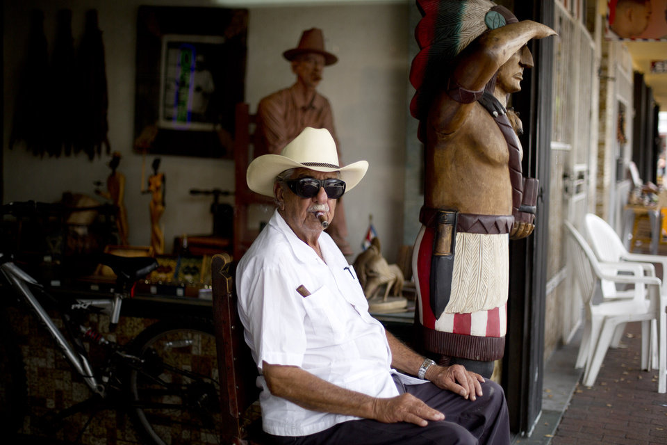 Photo - FILE - This April 30, 2014 photo shows Pedro Bello sits outside his Cuba Tobacco Cigar Factory on Calle Ocho (Eighth Street) in Miami's Little Havana. Once a refuge for Cuban exiles rekindling the tastes and sounds a lost home, today Miami's Little Havana is a mosaic of cultures and a popular tourist destination. (AP Photo/J Pat Carter)