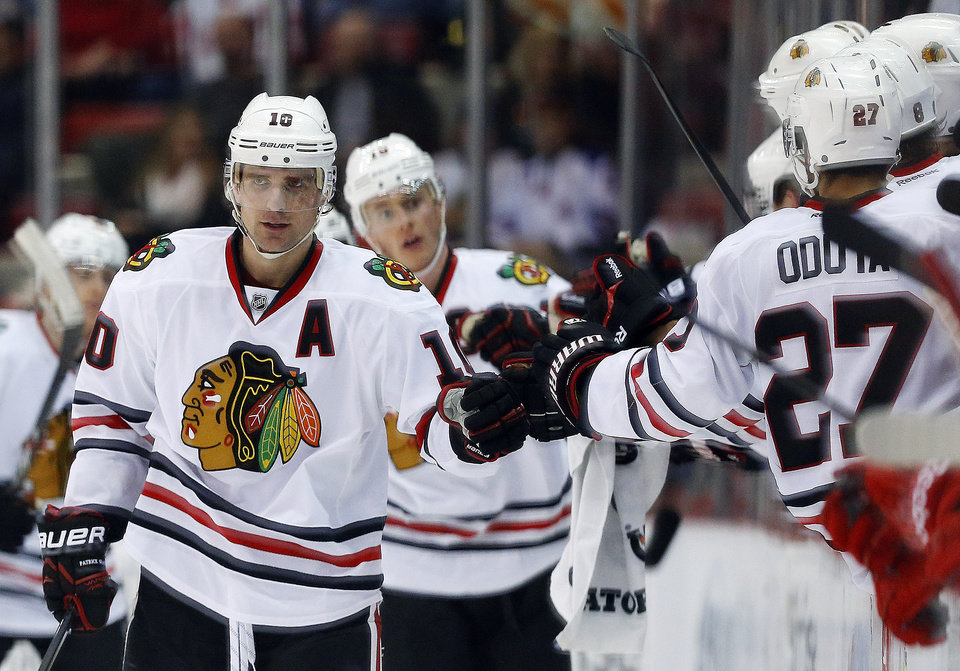 Photo - Chicago Blackhawks left wing Patrick Sharp (10) celebrates his goal against the Detroit Red Wings in the second period of an NHL hockey game Wednesday, Jan. 22, 2014, in Detroit. (AP Photo/Paul Sancya)