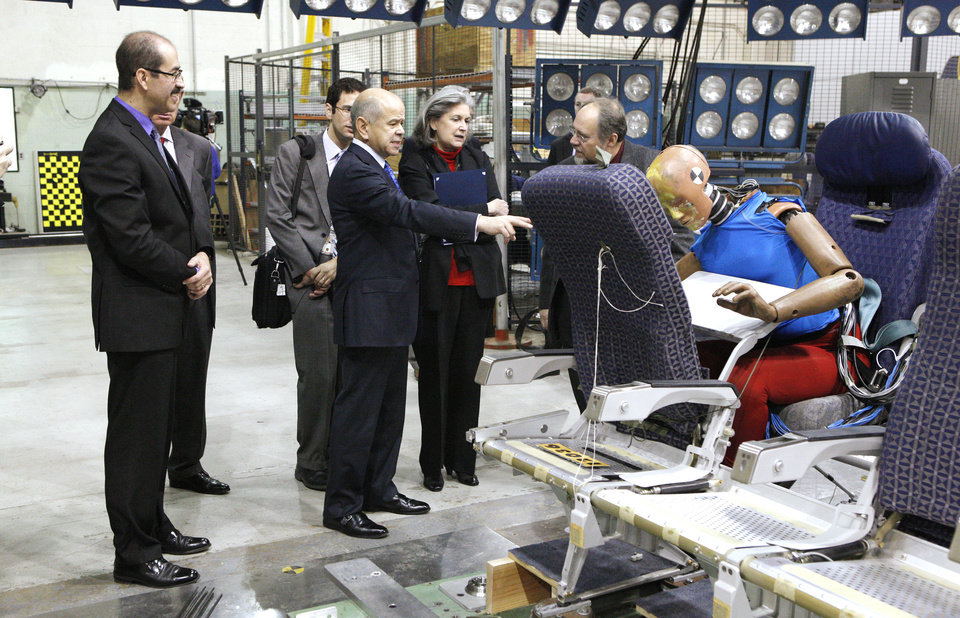 Dr. Melchor Antunano, far left, director of the FAA's Civil Aerospace Medical Institute, and Michael Huerta, center, acting administrator of the FAA, look at a test dummy Wednesday after a gravity impact sled test was conducted during a tour. PHOTOS BY PAUL B. SOUTHERLAND, THE OKLAHOMAN