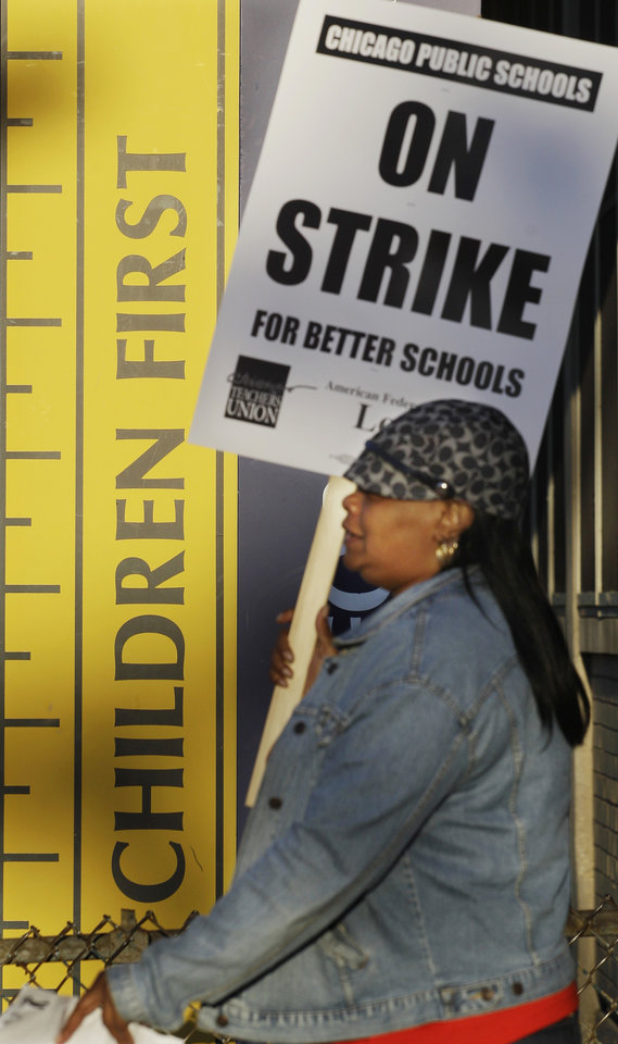 Photo -   Chicago teacher Alma Hill walks a picket line outside Benjamin Banneker Elementary School in Chicago, Monday, Sept. 10, 2012, after the teachers went on strike for the first time in 25 years. Union and district officials failed to reach a contract agreement despite intense weekend negotiations. (AP Photo/M. Spencer Green)