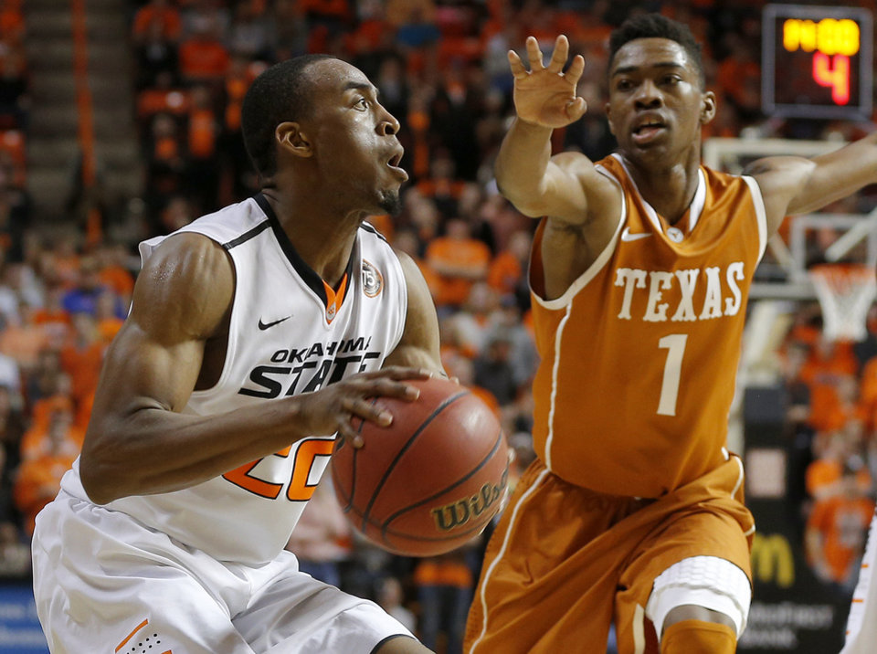 Oklahoma State's Markel Brown (22) looks to shoot beside Texas' Isaiah Taylor (1) during an NCAA college basketball game between the Oklahoma State Cowboys (OSU) and the University of Texas Longhorns at Gallagher-Iba Arena in Stillwater, Okla., Wednesday, Jan. 8, 2014. Oklahoma State won 81-74. Photo by Bryan Terry, The Oklahoman