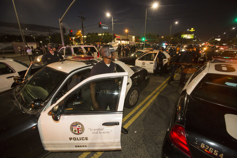 Photo - Police officers wait for demonstrators to arrive on Crenshaw Boulevard near the I-10 freeway during a protest in Los Angeles on Sunday, July 14, 2013, the day after George Zimmerman was found not guilty in the shooting death of Trayvon Martin. Seventeen-year-old Martin was shot and killed in February 2012 by neighborhood watch volunteer George Zimmerman.  (AP Photo/Ringo H.W. Chiu)