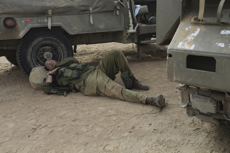 Photo - An Israeli soldier sleeps near the border of Israel and the Gaza Strip Wednesday, July 23, 2014. Israeli troops battled Hamas militants on Wednesday near a southern Gaza Strip town, sending Palestinian residents fleeing, as the U.S. secretary of state presses ahead with top-gear efforts to end the conflict that has killed hundreds of Palestinians and tens of Israelis. (AP Photo/Tsafrir Abayov)