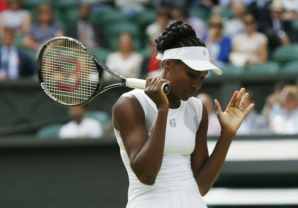 Photo - Venus Williams of U.S. gestures during her women's singles match against Petra Kvitova of the Czech Republic at the All England Lawn Tennis Championships in Wimbledon, London, Friday, June 27, 2014. (AP Photo/Sang Tan)