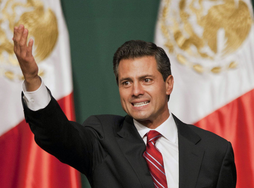 Photo -   Presidential candidate Enrique Pena Nieto waves to supporters at his party's headquarters in Mexico City, early Monday, July 2, 2012. Mexico's old guard sailed back into power after a 12-year hiatus Sunday as the official preliminary vote count handed a victory to Enrique Pena Nieto, whose party was long accused of ruling the country through corruption and patronage. (AP Photo/Christian Palma)