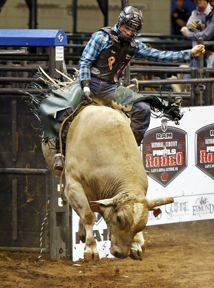 Photo - Sage Kimzey of Strong City, Okla., competes in bull riding during the National Circuit Finals Rodeo at the Lazy E Arena in Guthrie, Okla., Saturday afternoon, April 12, 2014. Photo by Nate Billings, The Oklahoman