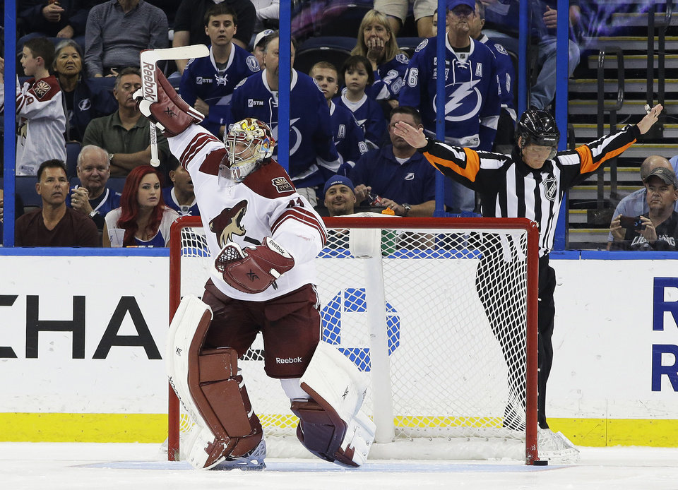Photo - Phoenix Coyotes goalie Mike Smith (41) celebrates after stopping Tampa Bay Lightning right wing Ryan Callahan (24) during a shoot out in an NHL hockey game Monday, March 10, 2014, in Tampa, Fla. The Coyotes won the game 4-3. Making the call is referee Rob Martell. (AP Photo/Chris O'Meara)