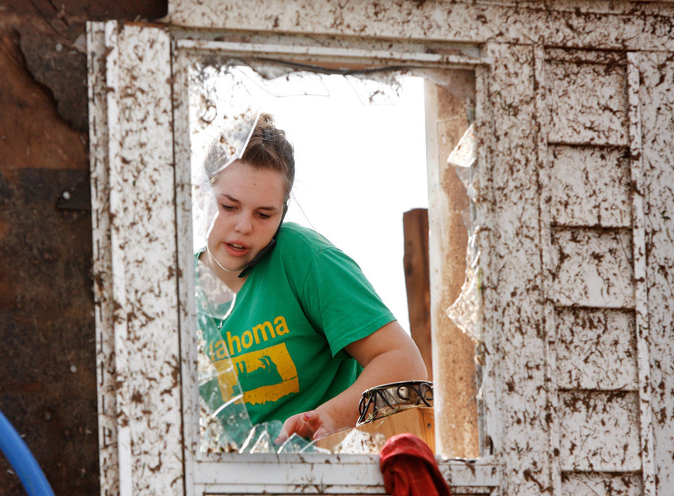 Photo - Rebecca Apel, 15, is seen through the broken glass of a door on the side of her family's home on SH 74 after a tornado destroyed the house late Tuesday afternoon,  May 24, 2011,  She and her brother were looking for salvageable items to take with them.  Photo by Jim Beckel, The Oklahoman