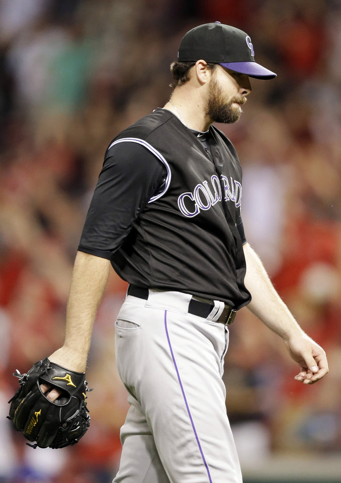 Photo - Colorado Rockies relief pitcher Boone Logan walks off the field after giving up a walkoff solo home run to Cincinnati Reds' Joey Votto in the ninth inning of a baseball game on Friday, May 9, 2014, in Cincinnati. Cincinnati won 4-3. (AP Photo/Al Behrman)