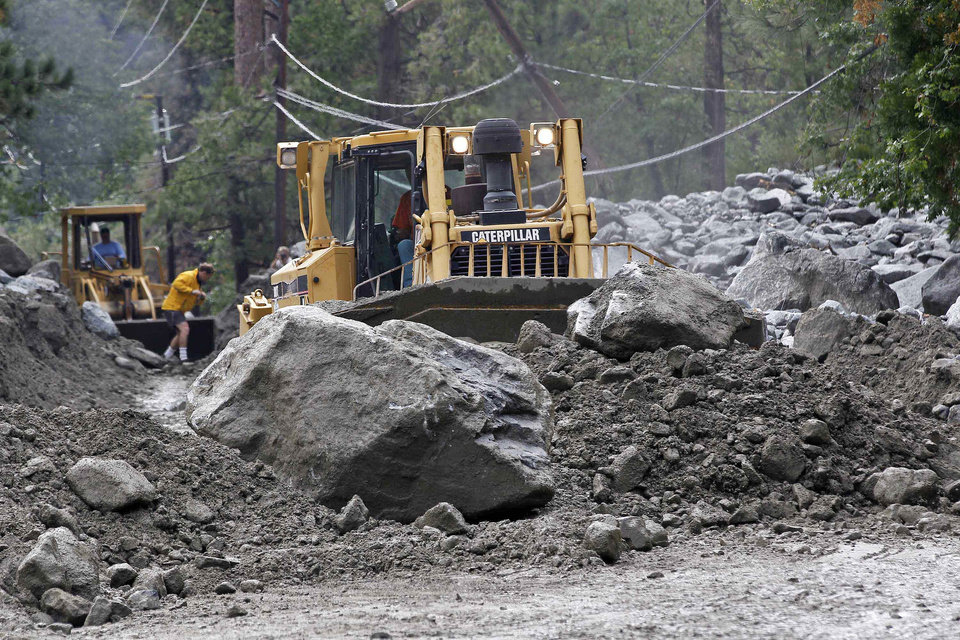 Photo - A bulldozer clears boulders and mud from a roan in the mountain community of Forest Falls in the San Bernardino Mountains, Monday, Aug. 4, 2014. Crews cleared roads in an area where some 2,500 had been stranded after thunderstorms caused mountain mudslides in Southern California over the weekend, while authorities estimated that between 6 and 8 homes were badly damaged and likely uninhabitable. One person was found dead in a vehicle that was caught in a flash flood. A group of campers spent the night at a community center near Forest Falls. (AP Photo/Nick Ut)