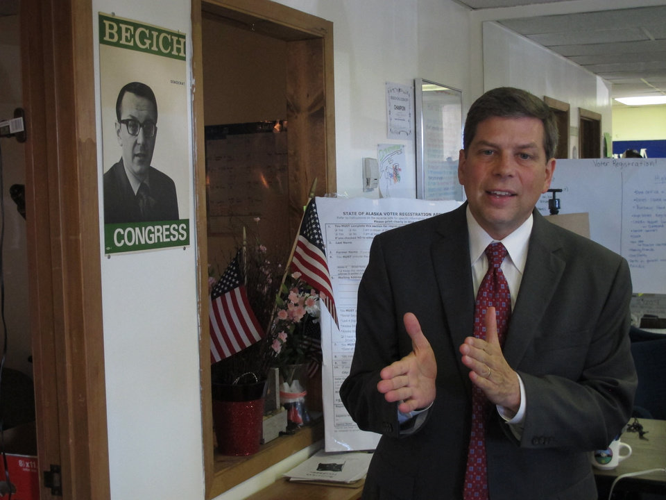 Photo - U.S. Sen. Mark Begich, D-Alaska, is shown in his campaign's volunteer office in Anchorage, Alaska, on Monday, Aug. 18, 2014, next to a campaign poster for his father, the late U.S. Rep. Nick Begich. Nick Begich was declared dead in 1972 after the plane he was flying in disappeared. (AP Photo/Becky Bohrer)