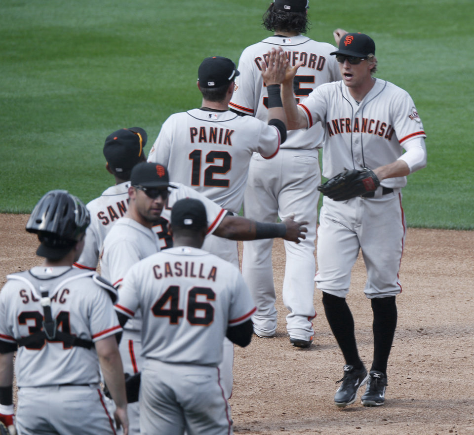 Photo - San Francisco Giants players congratulate right fielder Hunter Pence, right, after he led the Giants to a 4-2 victory over the Colorado Rockies in a baseball game in Denver on Monday, Sept. 1, 2014. The game was resumed in the bottom of the sixth inning of play when it was suspended because of rain on May 22. (AP Photo/David Zalubowski)