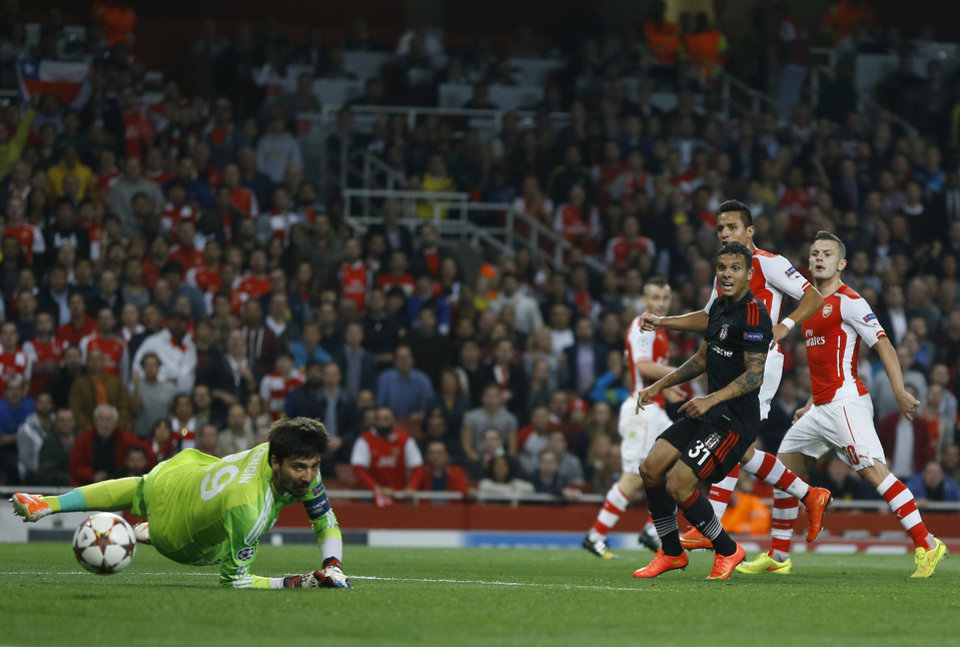 Photo - Arsenal's Alexis Sanchez, second right, scores a goal during a second leg Champions League qualifying soccer match between Arsenal and Besiktas at Emirates Stadium in London Wednesday, Aug. 27, 2014.(AP Photo/Kirsty Wigglesworth)