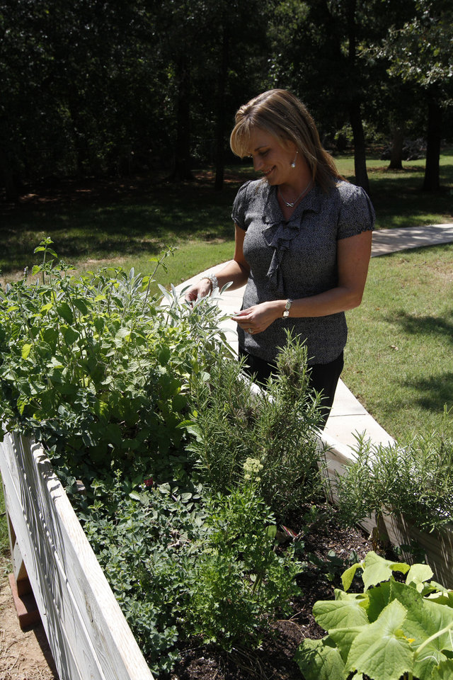 Shannon McClure, the owner of Eden Care, a non-traditional eldercare home, stands at the herb garden the residents have grown this summer. PHOTO BY PAUL HELLSTERN, THE OKLAHOMA. <strong>PAUL HELLSTERN - OKLAHOMAN</strong>