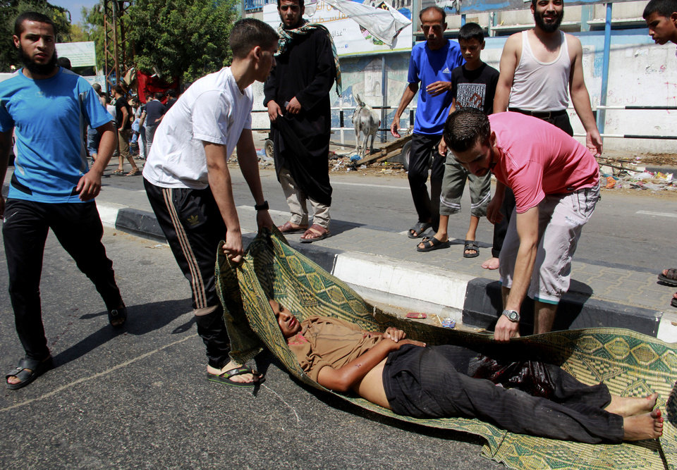 Photo - Palestinians evacuate a person killed in a blast outside a UN run school in Rafah, in the southern Gaza Strip, Sunday, Aug. 3, 2014. UNRWA's Director of Operations in the Gaza Strip said preliminary findings indicated the blast was a result of an Israeli airstrike near the school that been providing shelter for some 3,000 people. (AP Photo/Hatem Ali)