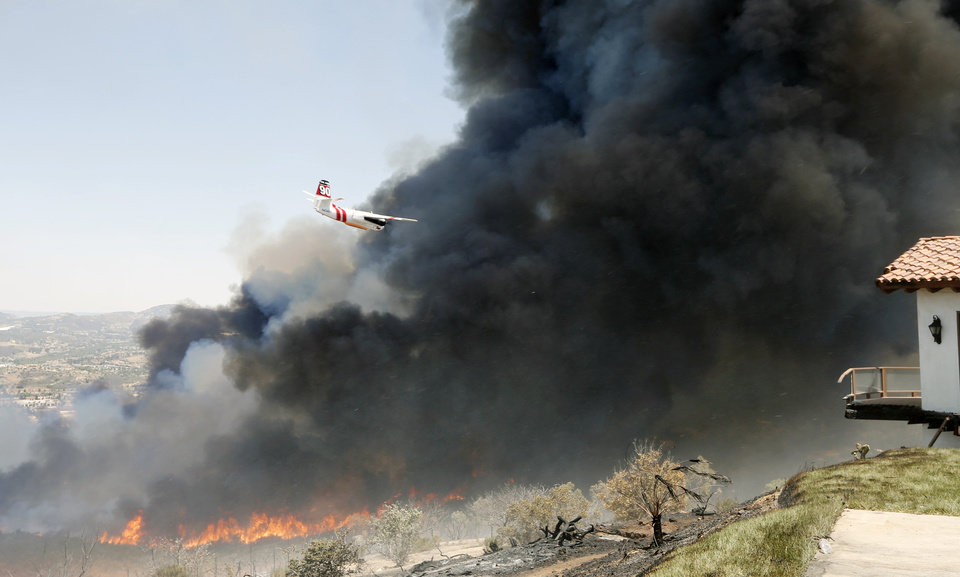 Photo - A firefighting aircraft moves into the smoke cloud as the wildfire flares with a wind shift Thursday, May 15, 2014, in San Marcos, Calif. Gusty winds failed to return Thursday in San Diego County wildfire areas and authorities said it was a window of opportunity to make further gains against flames that have charred thousands of acres and burned homes. (AP Photo)