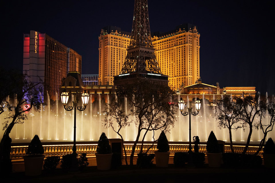 Photo -  A woman watches the fountains at the Bellagio hotel-casino along the Las Vegas Strip, Thursday, Nov. 19, 2020, in Las Vegas. As the coronavirus surges to record levels in Nevada, the governor has implored residents to stay home. But Democrat Steve Sisolak has also encouraged out-of-state visitors, the lifeblood of Nevada's limping economy, to come to his state and spend money in Las Vegas. (AP Photo/John Locher)