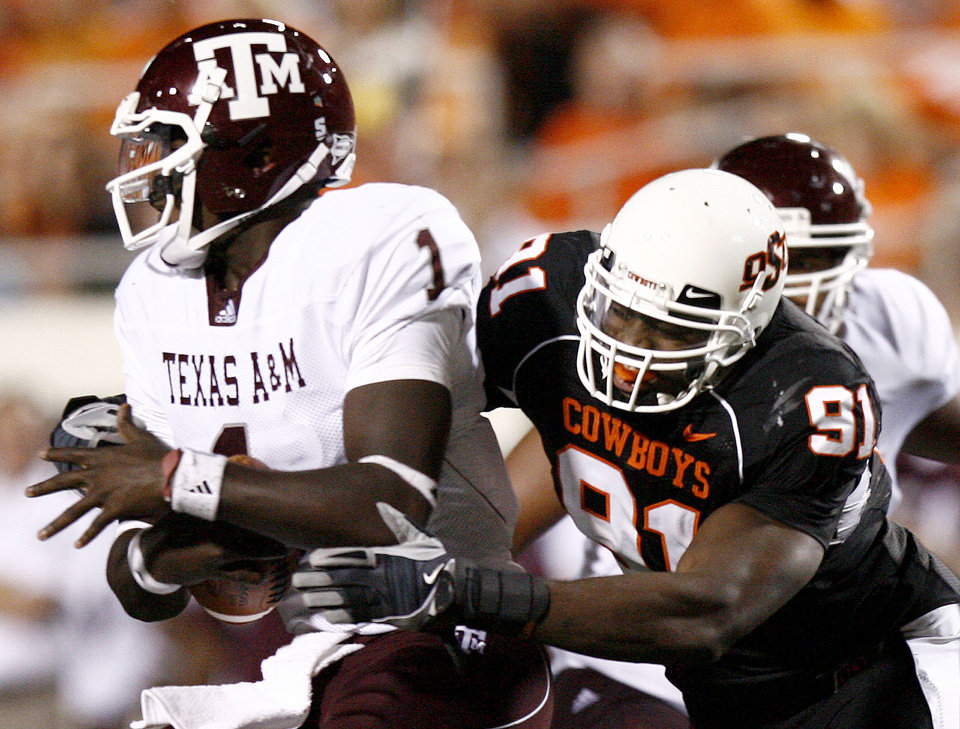 Photo - OSU's Ugo Chinasa (90) sacks A&M quaterback Jerrod Johnson (1) during the college football game between Texas A&M University (TAMU) and Oklahoma State University (OSU) at Boone Pickens Stadium in Stillwater, Okla., Thursday, Sept. 30, 2010. Photo by Sarah Phipps, The Oklahoman