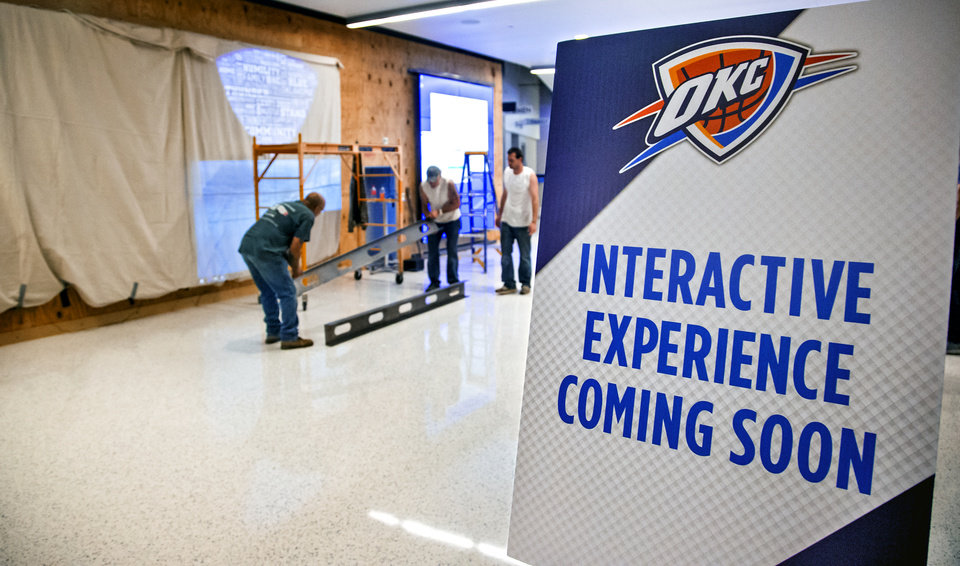 Photo -  Crews work to install the new interactive fan experience on the concourse level at Chesapeake Energy Arena in Oklahoma City. PHOTO BY CHRIS LANDSBERGER, The Oklahoman]