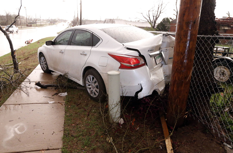Photo - A wrecked car is abandoned on SE 4th and after tornado force winds on Wednesday, March 25, 2015 in Moore, Okla. Photo by Steve Sisney, The Oklahoman