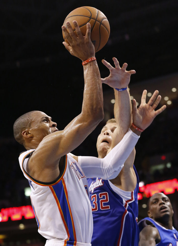 Photo - Oklahoma City Thunder guard Russell Westbrook (0) is fouled by Los Angeles Clippers forward Blake Griffin (32) in the third quarter of Game 1 of the Western Conference semifinal NBA basketball playoff series in Oklahoma City, Monday, May 5, 2014. Los Angeles won 122-105. (AP Photo/Sue Ogrocki)
