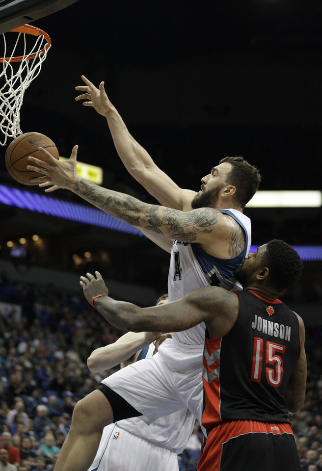 Photo - Minnesota Timberwolves center Nikola Pekovic (14) goes up for a rebound against Toronto Raptors forward Amir Johnson (15) in the first half of an NBA basketball game on Sunday, March 9, 2014, in Minneapolis. (AP Photo/Stacy Bengs)