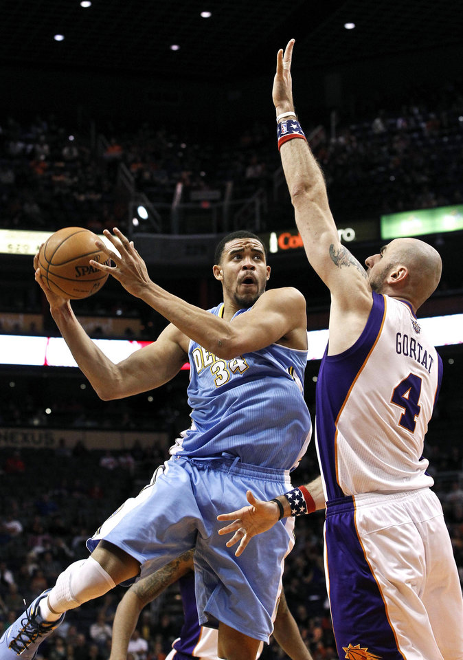 Denver Nuggets\' JaVale McGee (34) shoots against Phoenix Suns\' Marcin Gortat (4), of Poland, during the first half of an NBA basketball game on Monday, Nov. 12, 2012, in Phoenix.(AP Photo/Ross D. Franklin)