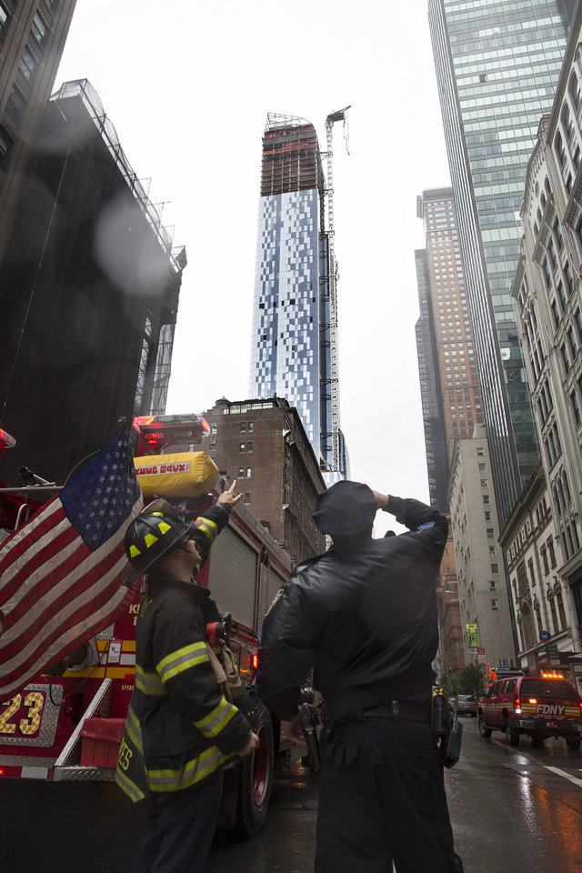 A FDNY firefighter and a New York police officer look up at a construction crane atop a luxury high-rise dangling precariously over the streets after collapsing in high winds from Hurricane Sandy, Monday, Oct. 29, 2012, in New York. Hurricane Sandy bore down on the Eastern Seaboard's largest cities Monday, forcing the shutdown of mass transit, schools and financial markets, sending coastal residents fleeing, and threatening a dangerous mix of high winds, soaking rain and a surging wall of water up to 11 feet tall. (AP Photo/John Minchillo) ORG XMIT: NYJM113