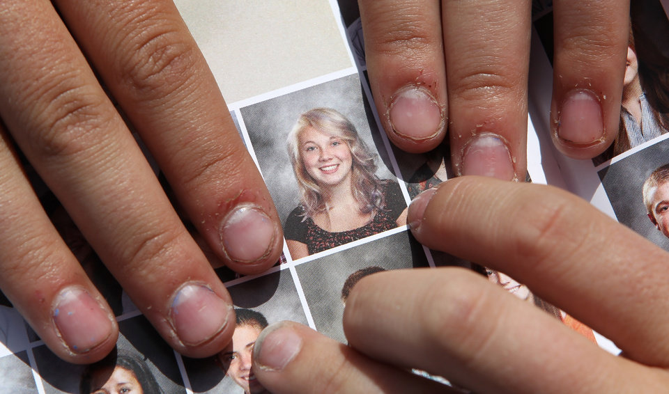 Photo - FILE - In this May 29, 2014 file photo, Wasatch High School sophomore Rachel Russell, 16, points to her altered school yearbook photo, center, in Heber City, Utah. Russell is one of several students at the school whose yearbook photos were digitally altered, with sleeves and higher necklines drawn on to cover up bare skin. Russell said Tuesday, June, 3, that she has since received a phone call from the school's principal, who explained he was sorry for the ordeal. (AP Photo/Rick Bowmer, File)