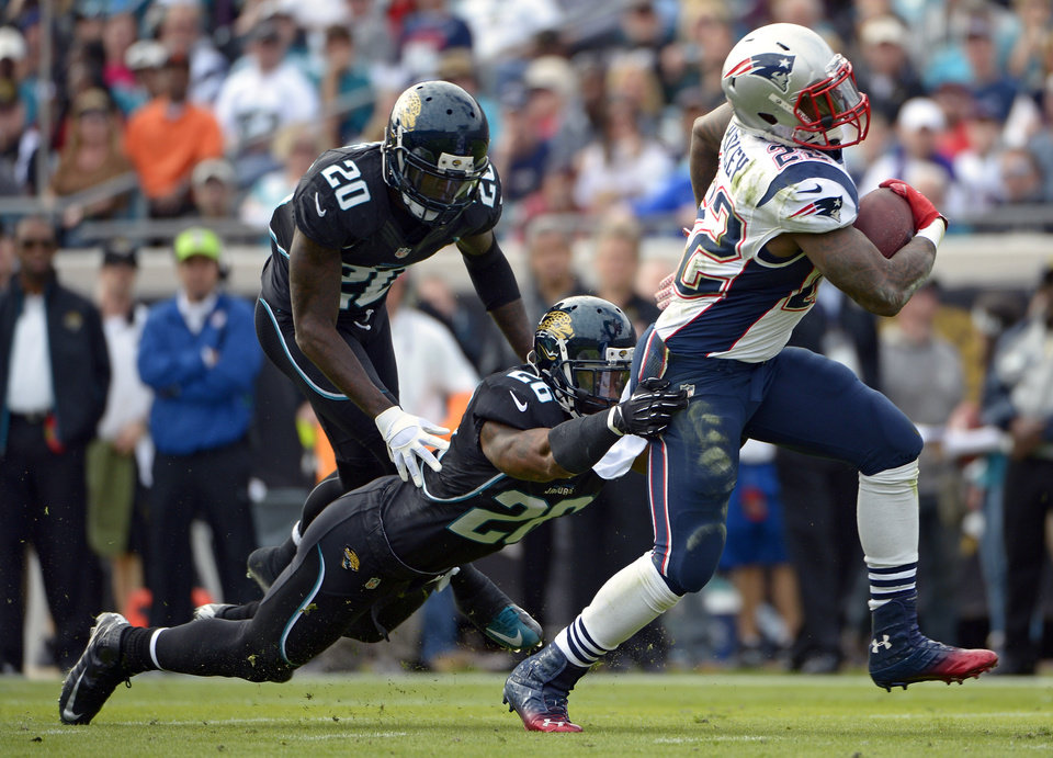 Photo - New England Patriots running back Stevan Ridley (22) runs for yardage past Jacksonville Jaguars strong safety Dawan Landry (26) and cornerback Mike Harris (20) during the first half of an NFL football game on Sunday, Dec.  23, 2012, in Jacksonville, Fla. (AP Photo/Phelan M. Ebenhack)