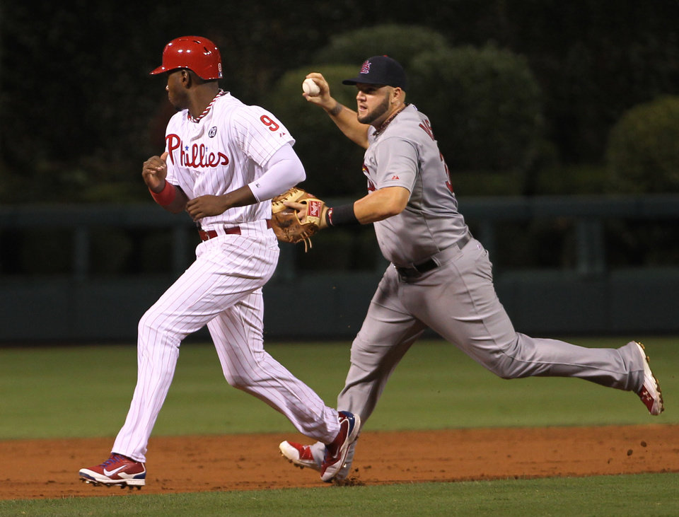 Photo - St. Louis Cardinals' Matt Adams runs past Philadelphia Phillies' Domonic Brown on a throwing error to third as Ryan Howard scores on a hit by Carlos Ruiz in the third inning of a baseball game, Friday, Aug. 22, 2014, in Philadelphia. (AP Photo/Laurence Kesterson)