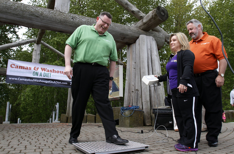Photo -   Camas Mayor Scott Higgins, left, steps on the scales as Washougal Mayor Sean Guard, right, and health coach Michelle Clark watch during their weigh-in in Washougal, Wash., Wednesday, May 2, 2012. The mayors of the two neighboring Washington state towns on the banks of the Columbia River are embarking on a