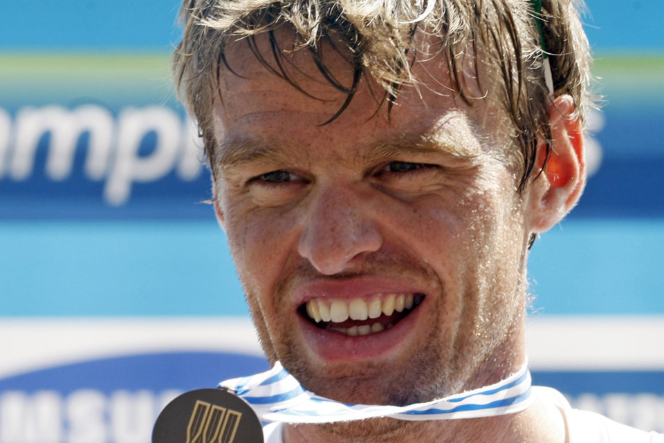 Photo - FILE -  In this Saturday, Sept. 3, 2011 file photo, British rower Alan Campbell displays his bronze medal on the podium after the Men's Single Sculls Final event at the World Rowing Championships in Bled, Slovenia. Campbell, whose abscessed lower-left wisdom tooth threatened to keep him from the 2008 Beijing Olympics, is certain that taking better care of his teeth has helped him row faster.  (AP Photo/Filip Horvat, File)