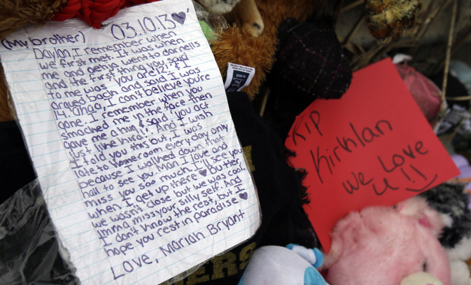 Photo - A note rests on a memorial where six teens died early Sunday in Warren, Ohio, on Monday, March 11, 2013. Two teens who escaped a crash that killed six friends in a swampy pond wriggled out of the wreckage by smashing a rear window and swimming away from the SUV, a state trooper said Monday. (AP Photo/Tony Dejak)