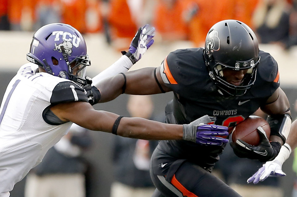 Photo - Oklahoma State's Blake Jackson (18) stiff arms TCU's Chris Hackett (1) during a college football game between Oklahoma State University (OSU) and Texas Christian University (TCU) at Boone Pickens Stadium in Stillwater, Okla., Saturday, Oct. 27, 2012. Photo by Sarah Phipps, The Oklahoman
