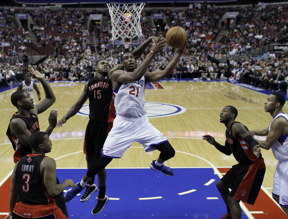Philadelphia 76ers' Thaddeus Young (21) shoots as Toronto Raptors' Amir Johnson (15) defends in the second half of an NBA basketball game on Friday, Jan. 18, 2013, in Philadelphia. Philadelphia won 108-101 in overtime. (AP Photo/Matt Slocum)