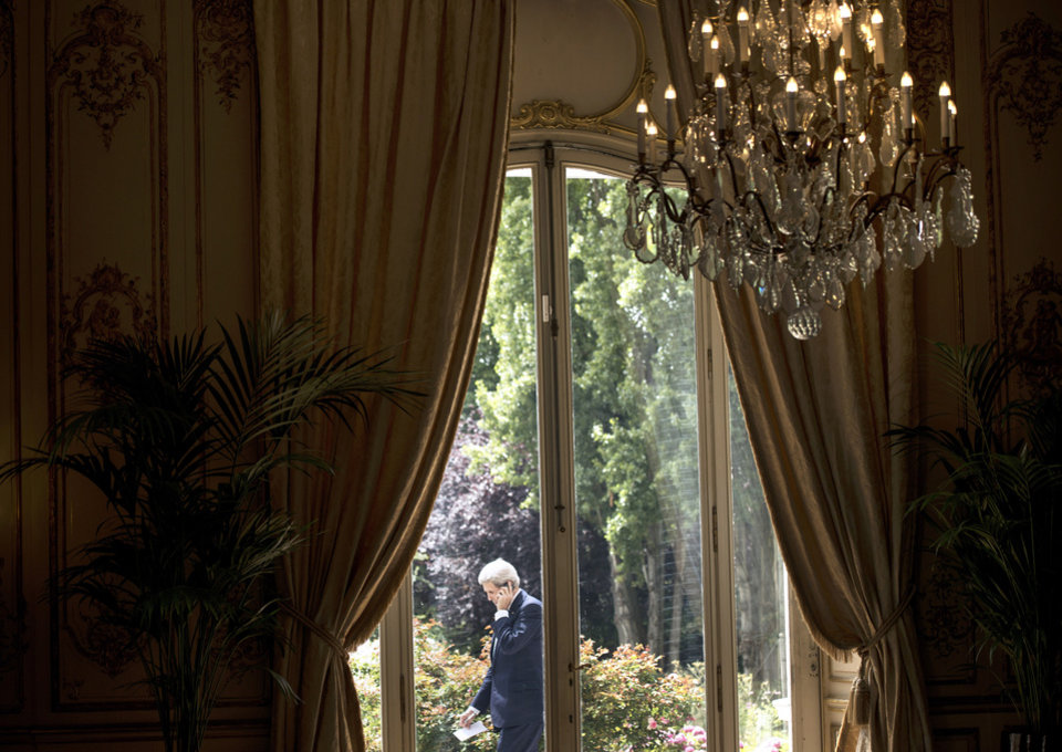 Photo - This photo taken on Thursday, June 26, 2014 shows through a window US Secretary of State John Kerry speaking on the terrace of the US Chief of Mission Residence in Paris, France. US Secretary of State John Kerry arrived in Paris on June 26, 2014 after stops in Baghdad, Arbil and Brussels to brief his Saudi, French and Israeli counterparts on his talks in Iraq and discuss the bloody three-year war in Syria. (AP Photo/Brendan Smialowski, pool)