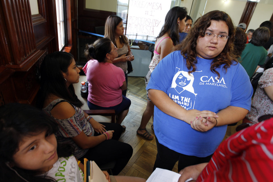 Photo -   Casa de Maryland volunteer Nathaly Uribe helps applicants with the documents they need to apply this afternoon for the Deferred Action Childhood Arrivals, Wednesday, Aug. 15, 2012, at Casa de Maryland in Langley Park, Md. Hundreds of thousands of young illegal immigrants scrambled to get papers in order Wednesday as the U.S. started accepting applications to allow them to avoid deportation and get a work permit _ but not a path to citizenship. (AP Photo/Jose Luis Magana)