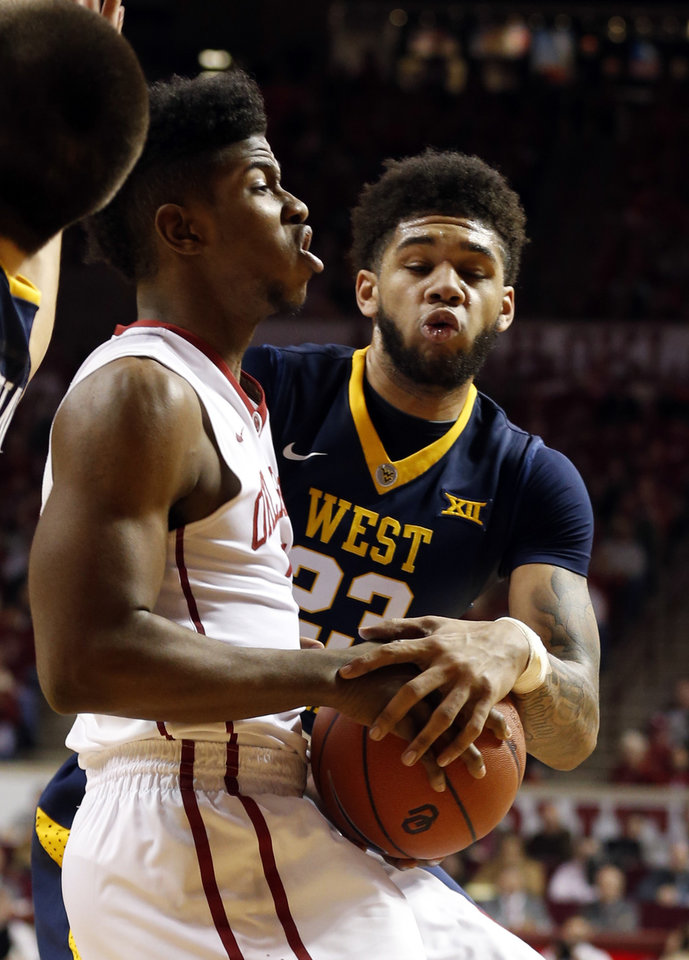 Photo - Oklahoma's Christian James (3) is fouled by West Virginia's Esa Ahmad (23) as the University of Oklahoma Sooner (OU) men play the West Virginia Mountaineers (WV) in NCAA, college basketball at The Lloyd Noble Center on Jan. 16, 2016 in Norman, Okla. Photo by Steve Sisney, The Oklahoman