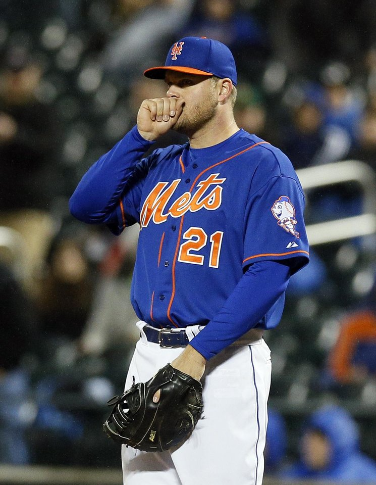 Photo - New York Mets first baseman Lucas Duda tries to warm up his hand at the start of a baseball game against the Cincinnati Reds at Citi Field in New York, Friday, April 4, 2014. (AP Photo/Paul J. Bereswill)