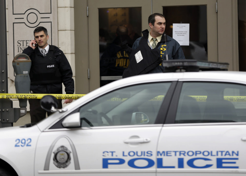 Photo - Police investigate outside the scene of a shooting Tuesday, Jan. 15, 2013, in St. Louis. Police say a gunman walked into the Stevens Institute of Business and Arts business school in downtown St. Louis and shot an administrator in the chest before shooting himself. (AP Photo/Jeff Roberson)
